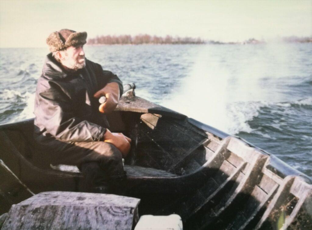 En äldre man kör öppen båt.