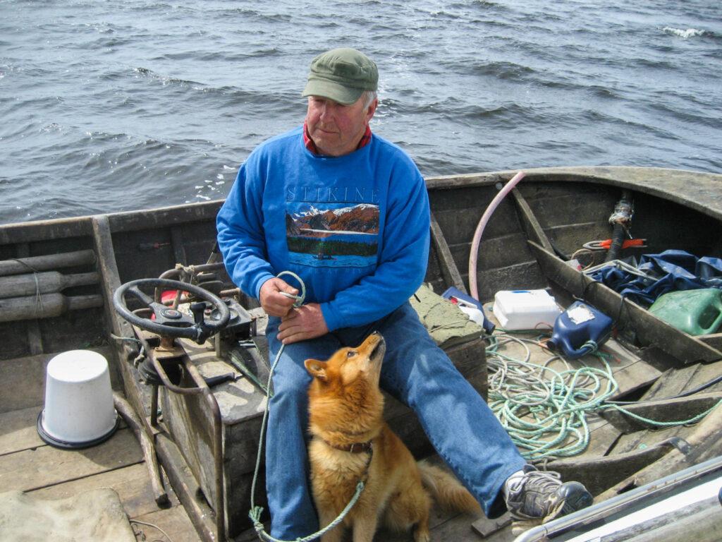 en man och en hund i en öppen båt