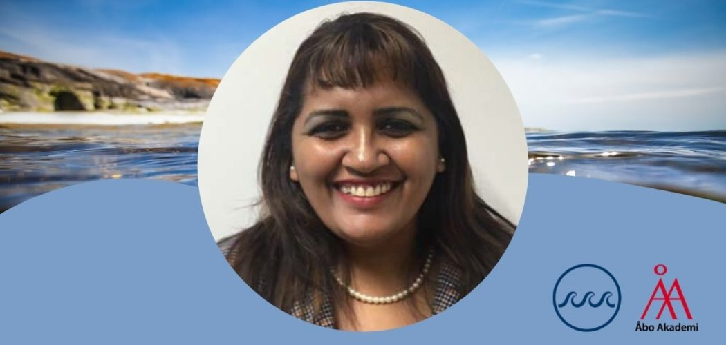 Porträttbild på Savitri Jetoo i mitten av bilden mot av bangrund av havet. i nedra högre hörnet forskningsprofilen havets logo och ÅAs logo