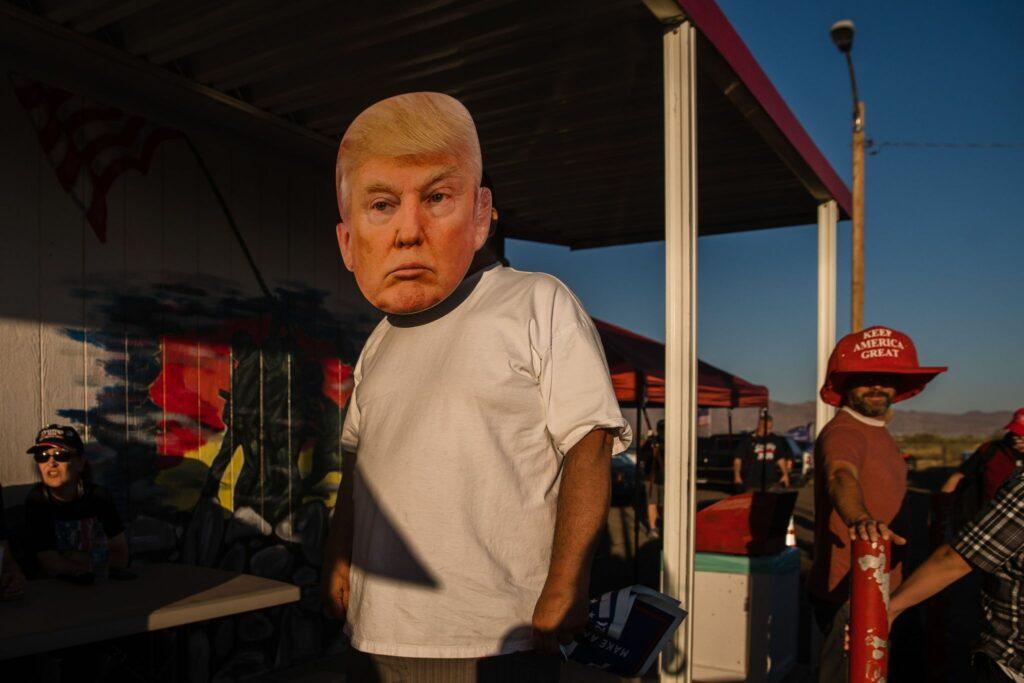 """Man i vit t-skjorta med Trump-mask i förgrunden. I bakgrunden en man med skämtsamt stor, röd keps med texten """"Keep America great""""."""