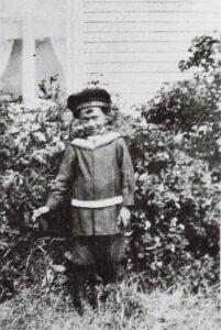 Gammal svartvit bild på en liten pojke i sjömanskostym.