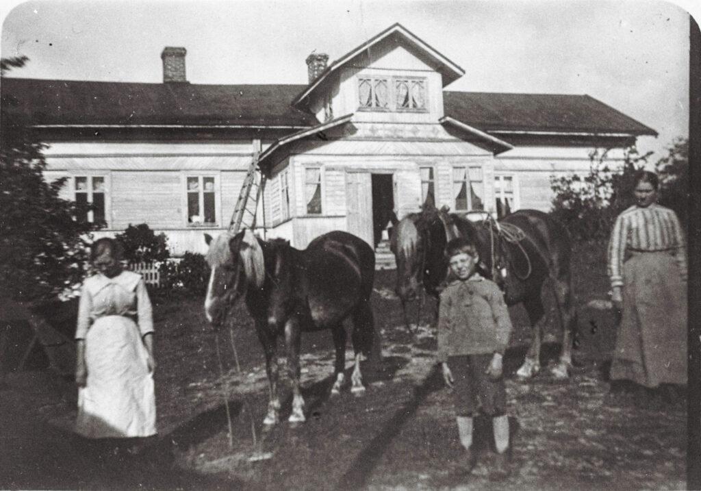 Gammal svartvit bild på ett hus, i förggrunden en häst och några personer.