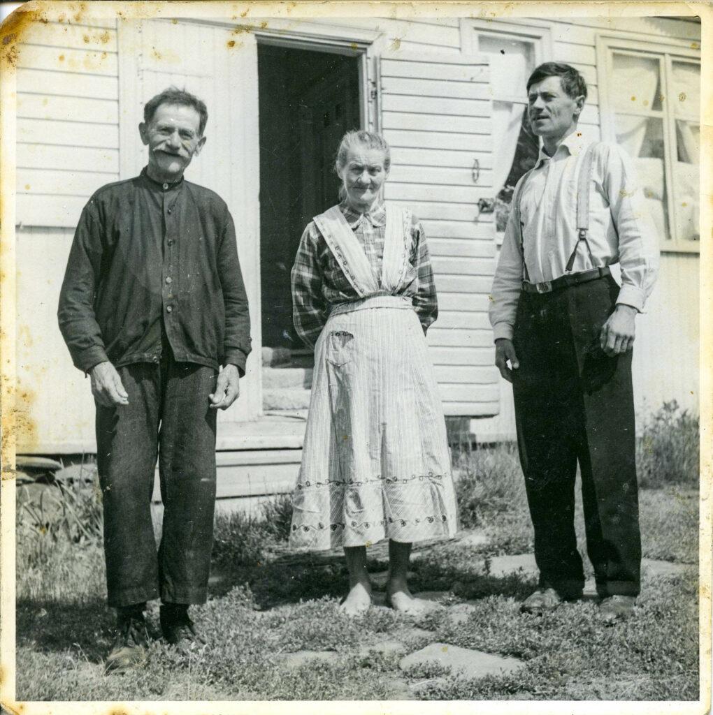 Ett gulnat fotografi på tre personer framför ett hus.