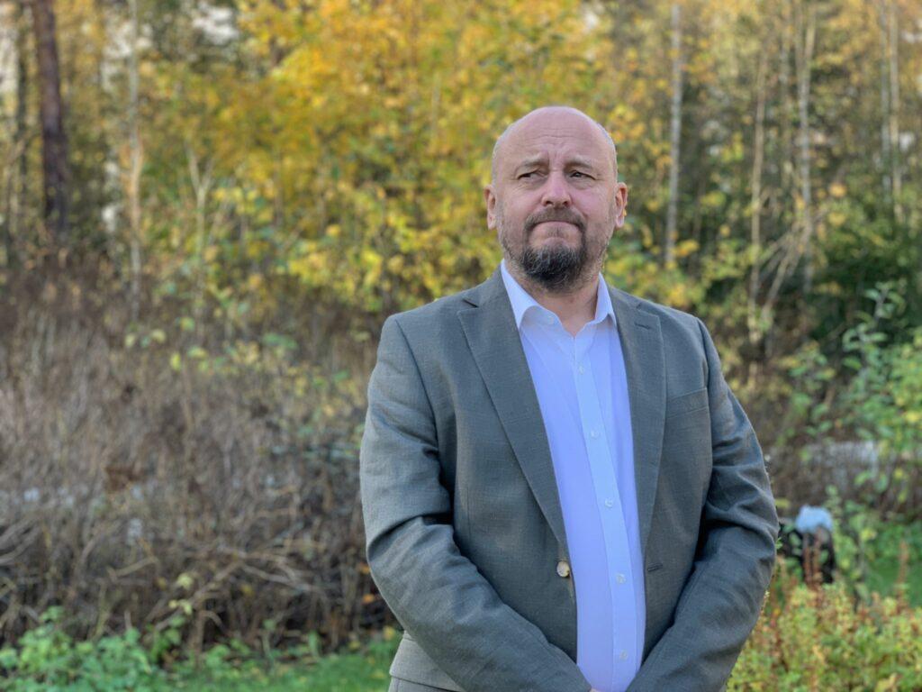 Claus Stolpe fotograferad på en höstig gård med gula löv och gråa kvistar i bakgrunden.