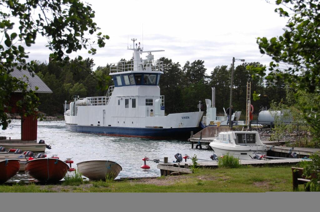 En stor förbindelsebåt ligger vid en brygga.