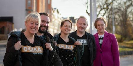Fem glada medlemmar i projektteamet med t-skjortor där det står O.lika.