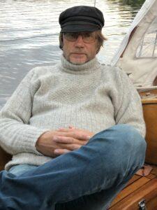 En man klädd i grå stickatröja sitter i en träbåt.