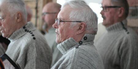 En man i profil med grå stickatröja på sig. Han sjunger i kör.