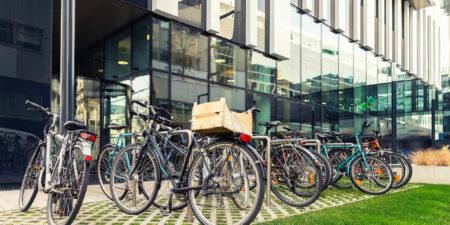 Cyklar parkerade utanför en modern byggnad.