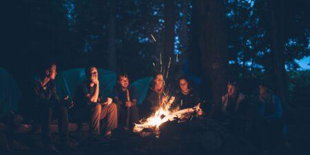 Ungdomar kring en lägereld i skymningen.