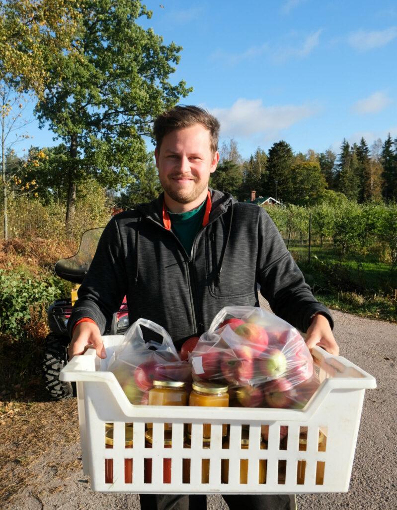 Mikael Hämäläinen med en låda äpplen i famnen.