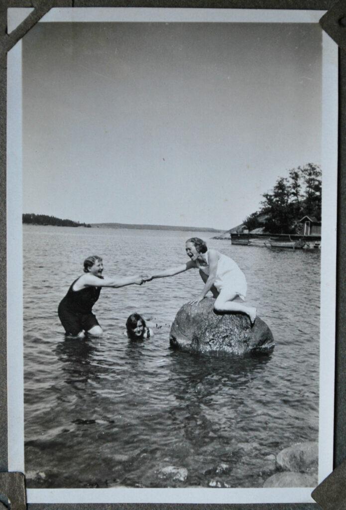 Tre kvinnor sinnar vid stranden, en av dem sitter på en sten ute i vattnet. Svartvit bild.