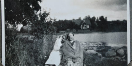 Svart-vit bild på två kvinnor där den ena lutar huvudet på den andras axel. I bakgrunden Själö kyrka.