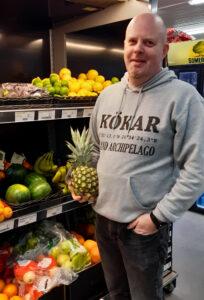 Raimo Virta vid frukshyllan i butiken med en ananas i handen.