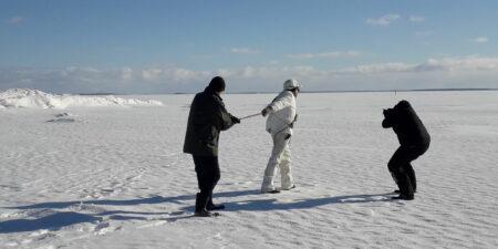 Två män går på isen på säljakt, en redje fotograferar dem.