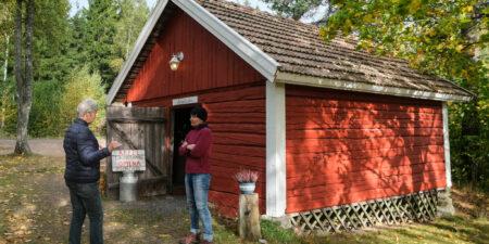 Två kvinnor utanför en rödmålad gammal bod.