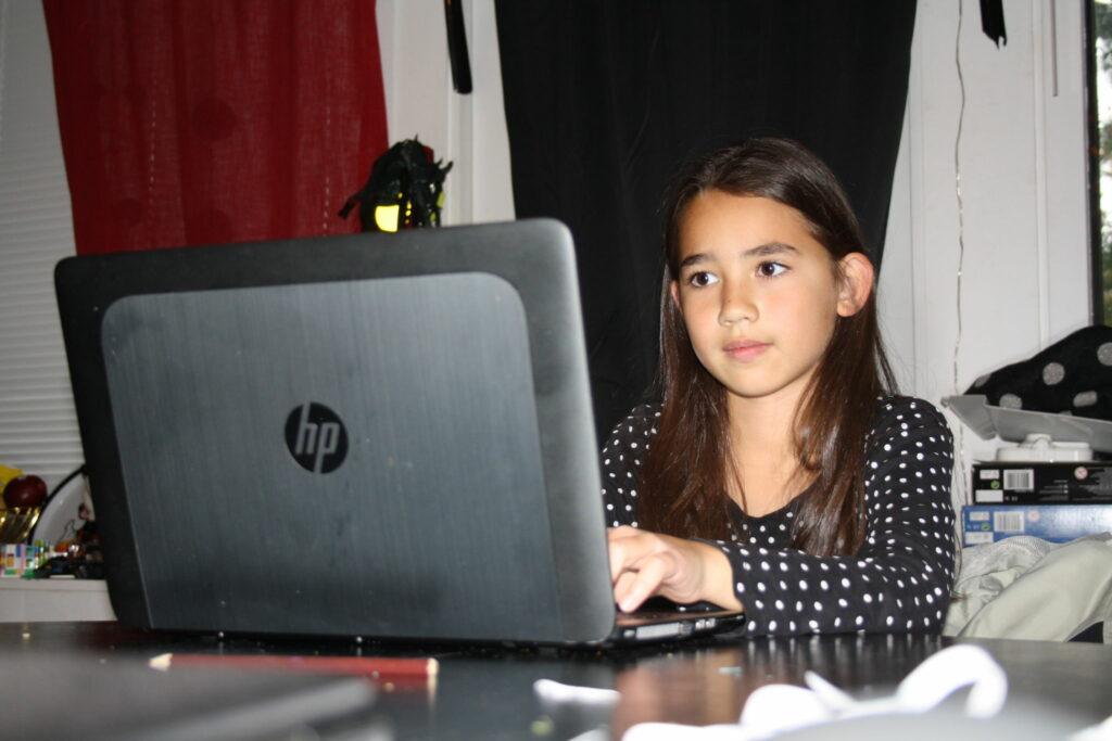 Barn sitter framför datorn.