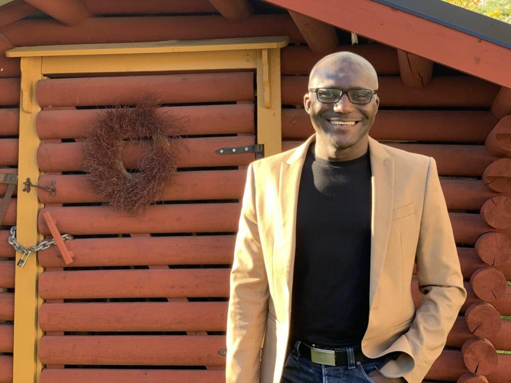 Emmanuel Acquah står framför en röd byggnad.