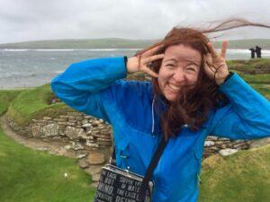En glad Pia Prost på en blåsig udde. Håret fladdrar i vinden.