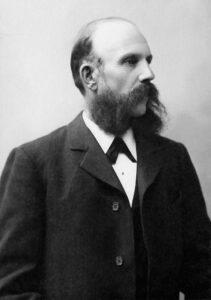 En svartvit, gammal bild på en uppklädd skäggig man i kostym.
