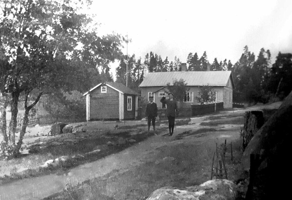 Två ganska otydliga personer på en väg framför ett större och ett mindre hus.