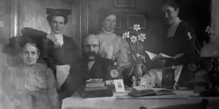 En familj på fem personer samlade för porträtt bakom ett bord. Svartvit bild.