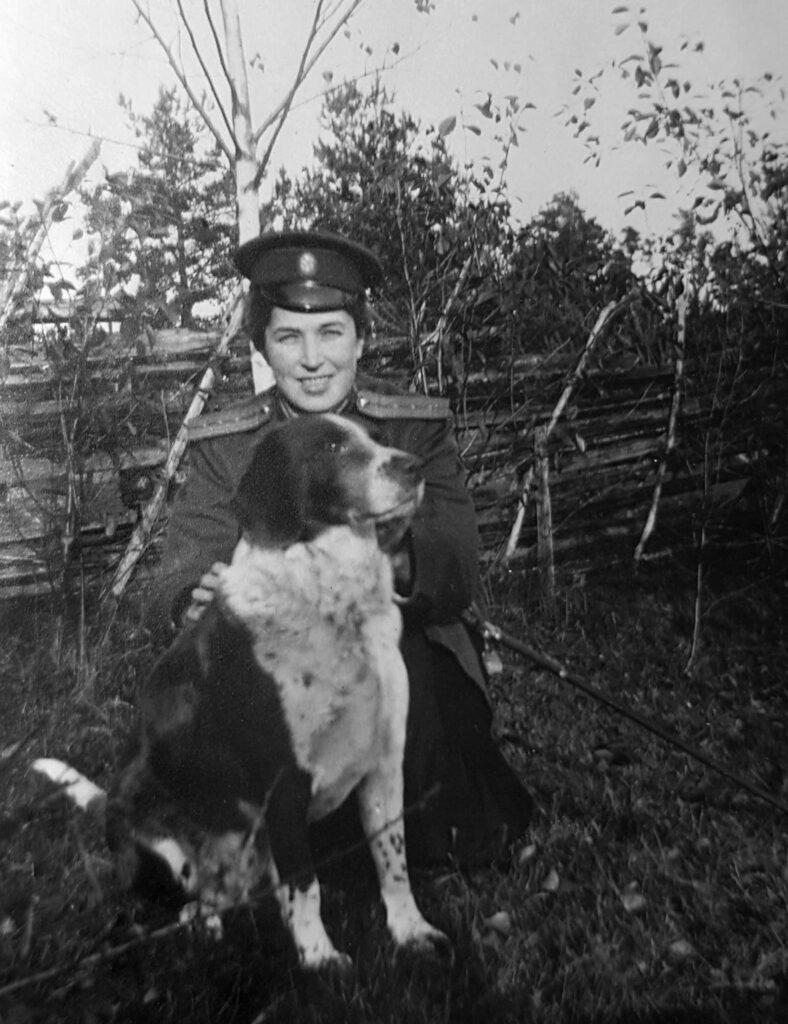 En ung kvinna i uniform på huk bakom en hund.