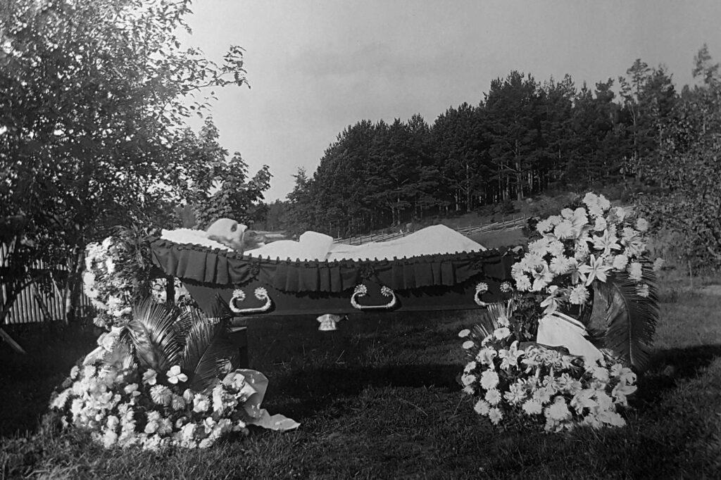 En gammal, svartvit bild på en död man i öppen kista med blomdekorationer kring.