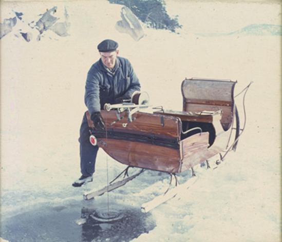 En man vid en isvak, lutande mot en släde med någon form av mätningsdon hängande från släden ner i vaken.