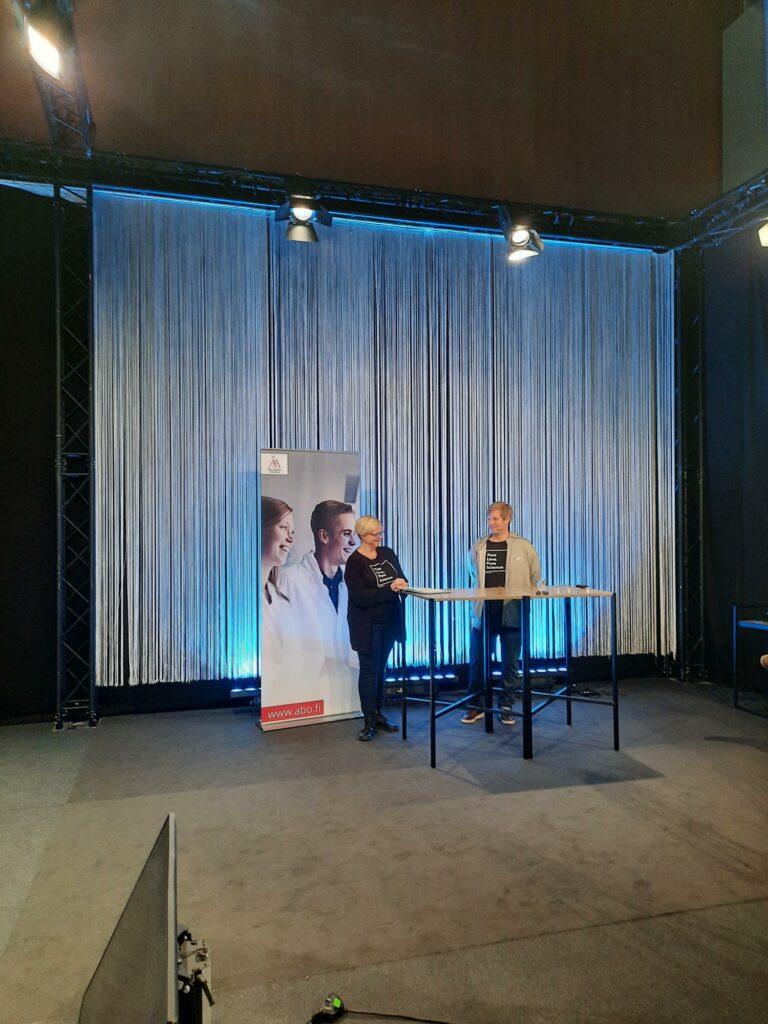 Foto från studion. Två personer bakom ett bord.