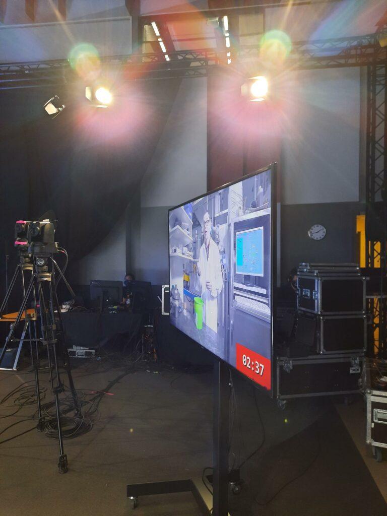 Foto från studion. TV-skärm med en laborerande forskare på.