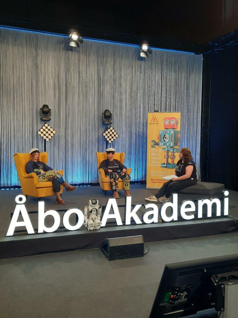 Foto från studion. Tre personer sitter på en scen.