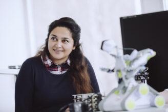 Studerande som sitter och ler med en robot på ett bord framför sig.