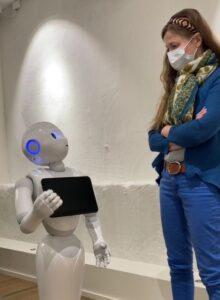 Roboten pepper håller fram en iPad åt en kvinna