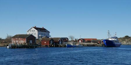 En fiskehamn fotad i vackert väder från havet.