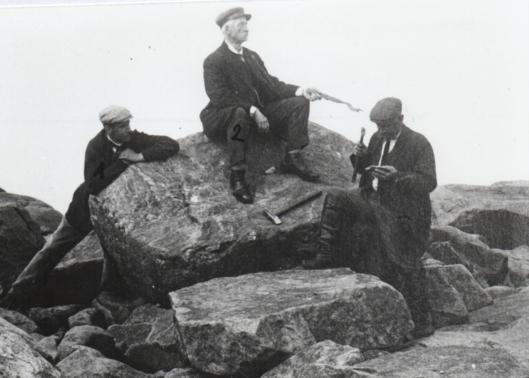 En gammal svartvit bild där tre män i kostym och keps sitter på en hög sten.