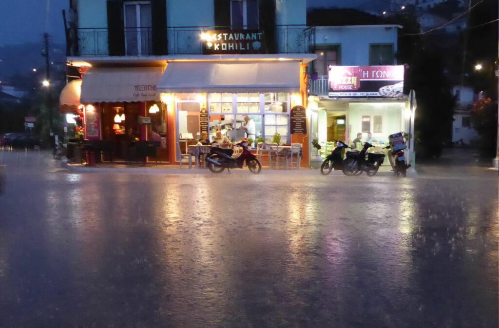 Ett gatukök med liten terrass fotad i ösregn på kvällen.