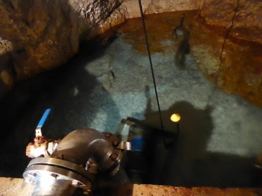 Ett tjockt järnrör går ner i ett hål i berget, hålet är vattenfyllt med klart vatten.