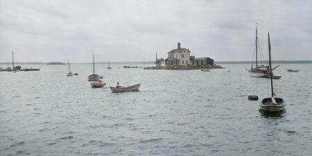 Många mindre båtar till havs kring en liten ö med ett hus på.