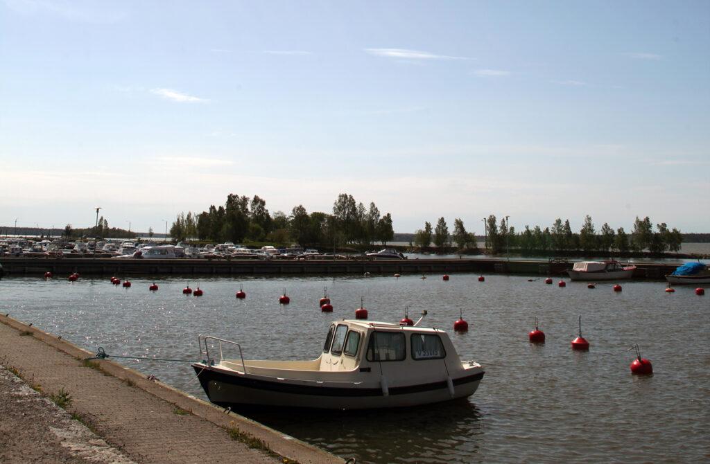 En småbåtshamn med en båt förtöjd i förgrunden.