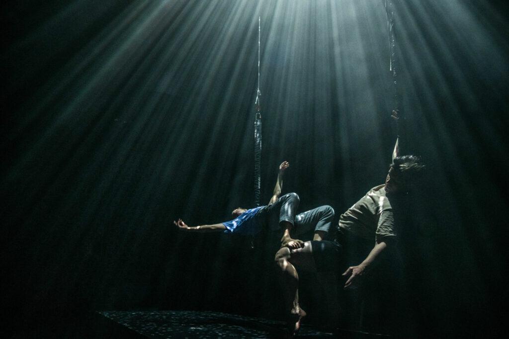 Två dansare på en scen, som är belyst så det ser ut att de dansar under vatten.