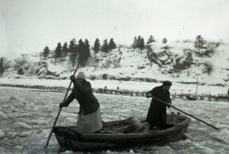Gammalt foto av två personer i ett isfyllt Aura å.