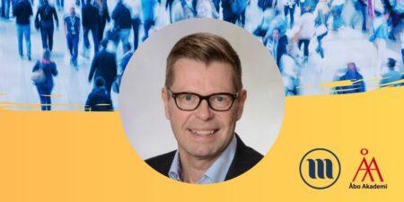 Rund porträttbild på Kimmo Grönlund. I bakgrunden uppe en folkmassa med suddiga människor. I bakgrunden nere gult och Minoritetsforskningens logo och ÅAs logo.
