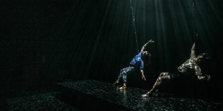 Två personer dansar på en scen som är ljussatt så det ser ut som att de dansar under vatten.