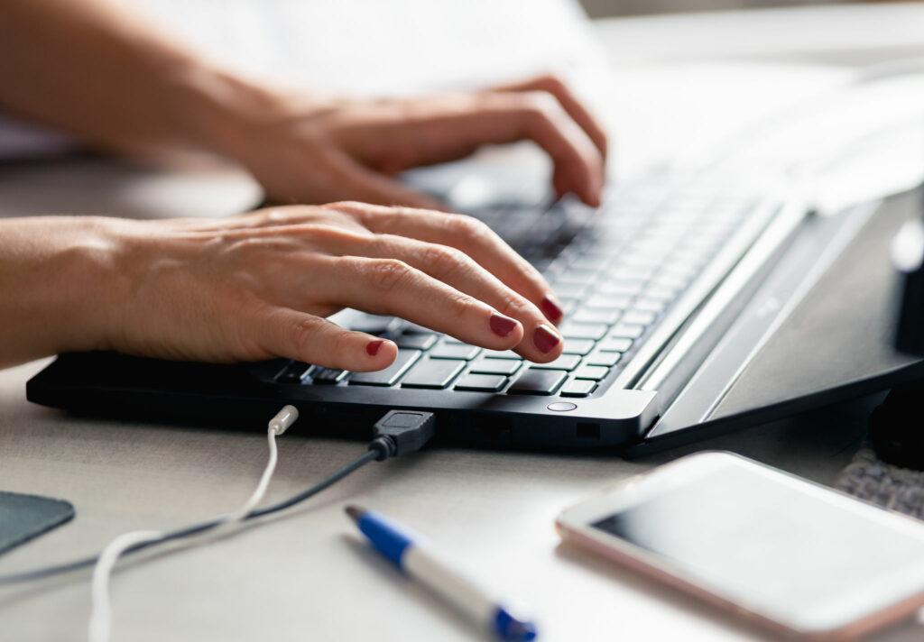 Bild av händer som skriver på en laptop.