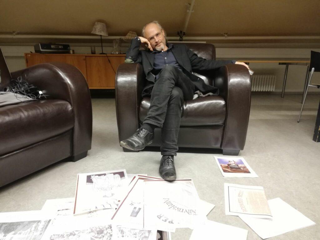 Fred Andersson sitter i en fåtölj med teckningar utbredda på golvet framför sig.