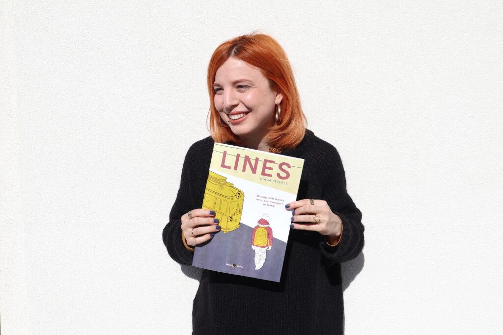 Muotokuva Giada Peterlestä pitäen sarjakuvateoksensa LINES käsissään.