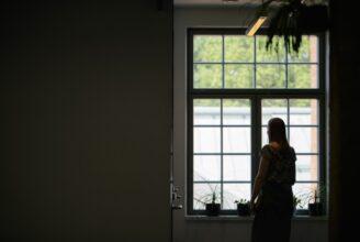 En studerande står vid ett fönster.