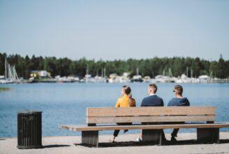 Studenter sitter på en bänk på stranden.