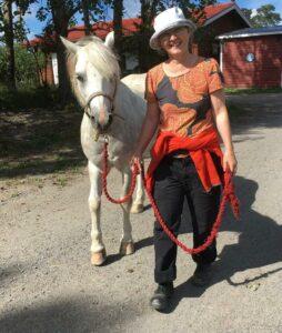 Ria Heilä-Ylikallio och en vit häst.
